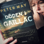 Kvinna med glasögon läser boken Döden i Gaillac av Peter May